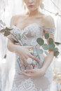 Bouquet of flowers in a vase holding a girl bride in an elegant white wedding dress with a big ring on his finger Royalty Free Stock Photo