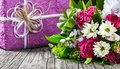 Bouquet of fresh flowers and gift box on an old wooden table Royalty Free Stock Photo
