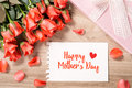 Bouquet of fresh pink red roses with gift on wooden background. Floral romantic arrangement with card text Happy Mother's Day Royalty Free Stock Photo