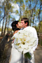Bouquet kala against romantic kiss bride and groom Royalty Free Stock Image