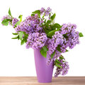 Bouquet of lilac flower in a jug on wooden surface Royalty Free Stock Images