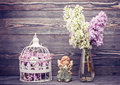 Bouquet lilac flowers, angel and bird cage. style nostalgia