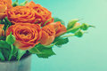 Bouquet of orange roses in a vase on vintage shabby chic background Stock Photo