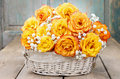 Bouquet of orange roses in a white wicker basket standing on wooden table Royalty Free Stock Photos