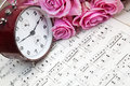 Bouquet of pink roses an antique alarm clock and old sheets of music Stock Photo