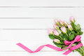 Bouquet of pink roses decorated with ribbon on white wooden background. Top view Royalty Free Stock Photo