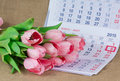A bouquet of pink tulips lying on the calendar Royalty Free Stock Photo