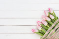 Bouquet of pink tulips on white wooden background top view Royalty Free Stock Images