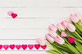 Bouquet of pink tulips on white wooden table decorated with hearts valentines day background top view copy space Royalty Free Stock Photos