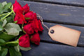 Bouquet of red roses with an empty vintage tag for your message Royalty Free Stock Images