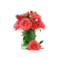 Bouquet of red roses in transparent glass vase festive a and one rose lying near Stock Images