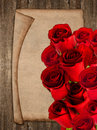 Bouquet of red roses and vintage paper sheet over rustic wooden background Royalty Free Stock Photos