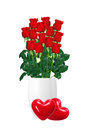Bouquet  of red roses in white vase and two red hearts closeup Royalty Free Stock Photo