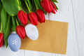 Bouquet red  tulip flowers with easter eggs on old wooden table Royalty Free Stock Photo