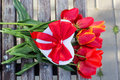 Red tulip flowers and gift box on wooden table