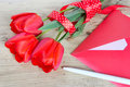 Bouquet of red tulips & envelope  wooden background. Royalty Free Stock Photo