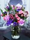 Bouquet with roses, blue flowers in a glass vase Royalty Free Stock Photo