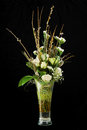Bouquet of roses statice and pussy willows branches in glass vase on black background Stock Photography