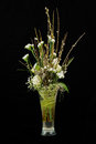 Bouquet of roses statice and pussy willows branches in glass vase on black background Royalty Free Stock Photo