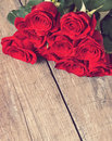 Red roses on the white wooden background