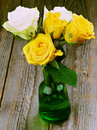 Bouquet of roses yellow and white with droplets in green glass vase closeup on rustic wooden background Royalty Free Stock Images