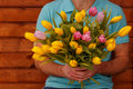 Bouquet of spring tulips in the hands of men on wooden background