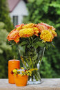 Bouquet of stunning orange roses in transparent glass vase garden party decor Royalty Free Stock Photo