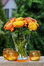 Bouquet of stunning orange roses in transparent glass vase garden party decor Stock Image