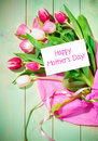Bouquet of tulips and card on green wooden background Stock Photo