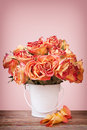 Bouquet vintage roses white metal pot wooden surface pink background Stock Photography