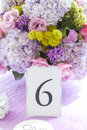 Bouquet of wedding flowers closeup on table at reception with number place setting Royalty Free Stock Image