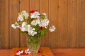 Bouquet of white flowers and red roses on the ragged old wooden wall background Royalty Free Stock Image