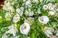 Bouquet of white flowers, roses, calla lilies and green leaves Royalty Free Stock Photo