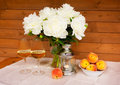 Bouquet of white peonies, glasses of wine, lantern  and peaches Royalty Free Stock Photo
