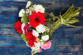 Bouquet of white, pink and red flowers on a wooden surface Stock Images