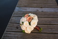 A bouquet of white and pink roses on wooden pier wedding lies the Stock Images