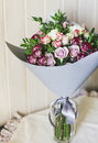 The bouquet of white and pink spray roses in a gray floral paper Royalty Free Stock Photo