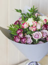 The bouquet of white and pink spray roses in gray floral paper Royalty Free Stock Photo