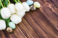 Bouquet white tulip flowers with easter eggs on old wooden tabl Royalty Free Stock Photo