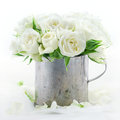 Bouquet of white wedding roses in an old vintage metal cup on dreamy lace background with floral petals Stock Image