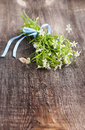 Bouquet of white wildflowers lying on a wooden table with blue bow Royalty Free Stock Photography