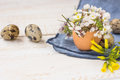 Bouquet of white yellow flowers in eggshell, quail eggs, blue napkin on wood table, Easter interior decoration Royalty Free Stock Photo