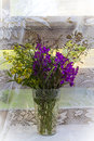 A bouquet of wild wildflowers in a transparent vase, in the summer, on the terrace. Royalty Free Stock Photo