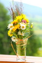 Bouquet of wildflowers bunch daisies and other in a glass vase on a ledge outdoors Royalty Free Stock Photo