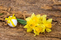 Bouquet of yellow daffodils and chicken egg with a ribbon Royalty Free Stock Photo