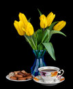 Bouquet of yellow tulips in glass vase and antique tea cup full of tea on black background Stock Images