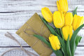 Bouquet of yellow tulips on white rustic wooden background Royalty Free Stock Photo