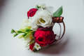 Boutonniere made of dark rose and white flower lies on the table Royalty Free Stock Photo