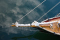 The bow of a schooner from above restored two masted showing beautiful teak wood deck and bowsprit sail on calm waters Stock Photos