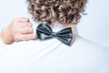 Bow tie on the back side strange or fun concept strangeness view of an elegant young fashion man in tuxedo gray background toned Royalty Free Stock Photography